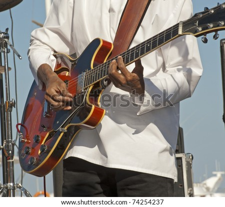 Guitarist in a band playing live music on stage - stock photo