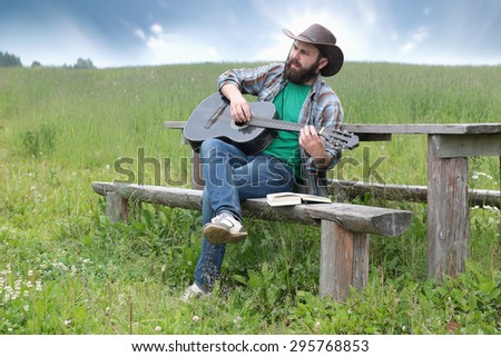 guitarist in a cowboy hat on the nature - stock photo