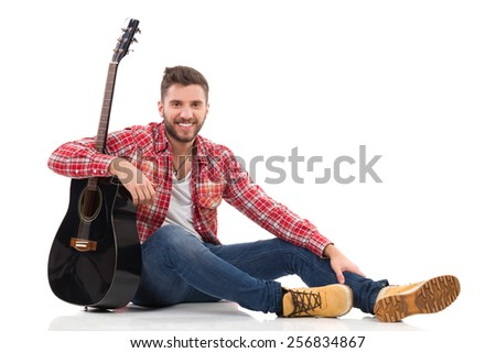 Guitarist in red lumberjack shirt sitting on a floor. Full length studio shot isolated on white. - stock photo