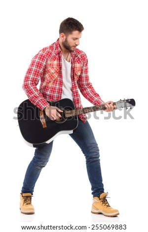 Guitarist in red lumberjack shirt standing with the black acoustic guitar. Full length studio shot isolated on white. - stock photo