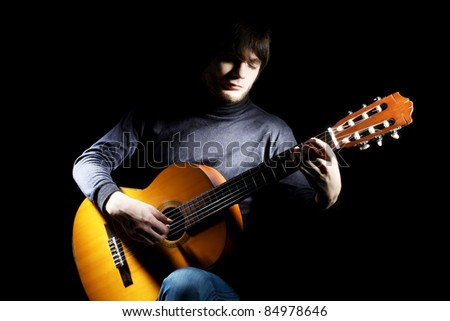 Guitarist musical instrument guitar acoustic. Musician man concert playing on black - stock photo