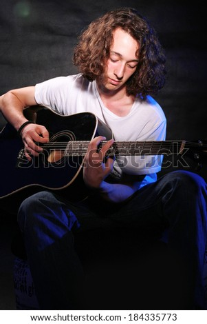 Guitarist musician guitar acoustic playing. Young man performer  - stock photo