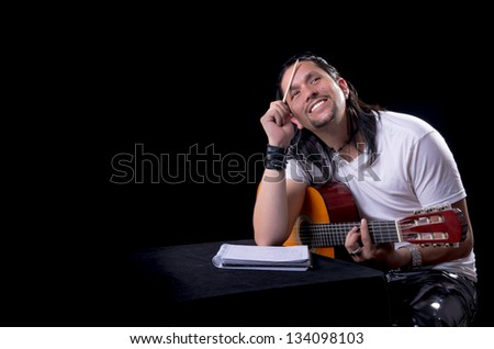 Guitarist musician writing a song on his guitar - stock photo