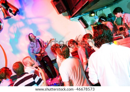 Guitarist on stage in a nightclub, with party crowd, saxophonist and DJ - stock photo