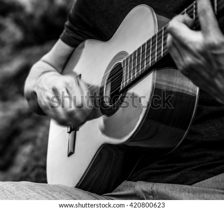 Guitarist play music siting on beach rock, close-up moving hands. Black-white outdoor photo. - stock photo