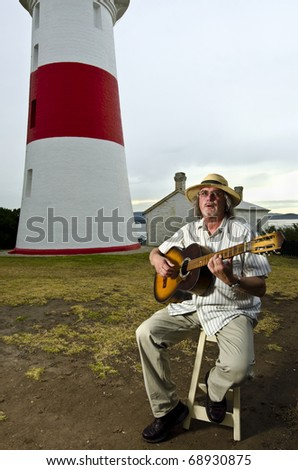 Guitarist playing acoustic instrument near lighthouse - stock photo