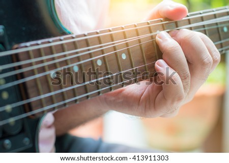 Guitarist playing an electric guitar. Shallow depth of field. - stock photo