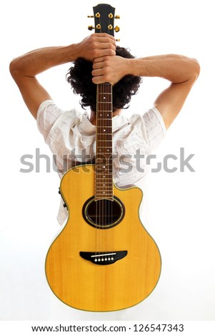 Guitarist with acoustic guitar on his back - stock photo