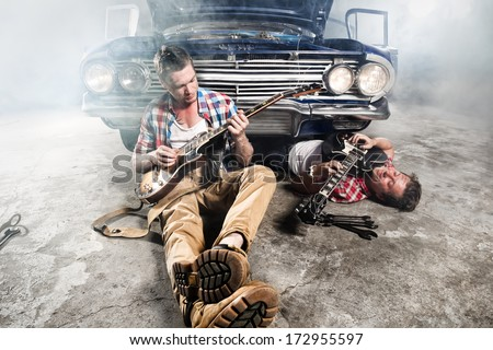Guitarists at a garage next to the retro car in smoke - stock photo