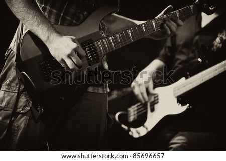 guitarists of a rock band with a guitar - stock photo