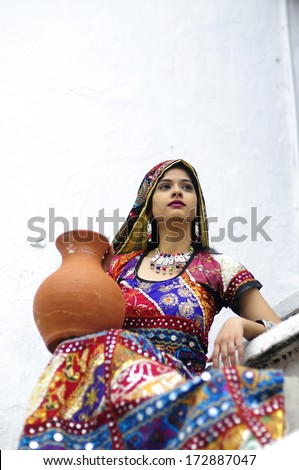 GUJARAT, INDIA - NOVEMBER 30: Unidentified Indian woman in colorful traditional dress carrying clay pots on November 30, 2011 in Gujarat, India - stock photo