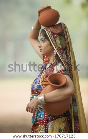 GUJARAT, INDIA - NOVEMBER 30: Unidentified Indian women in colorful traditional dress carry water in clay pots on November 30, 2011  in Gujarat, India - stock photo