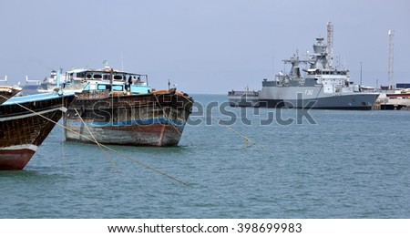 GULF OF ADEN, PORT OF DJIBOUTI - FEBRUARY 08, 2016: Traditional old style wooden fishing and cargo ships and EU WARSHIP F-262, German multipurpose corvette on background - stock photo