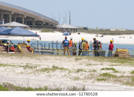 GULF SHORES - MAY 8: Workers gather on May 8, 2010 to protect beautiful Gulf Shores, Alabama from the BP oil spill that threatens the popular resort area. - stock photo