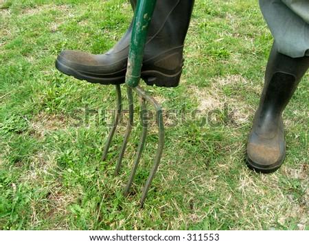 gum boots digging in garden - stock photo