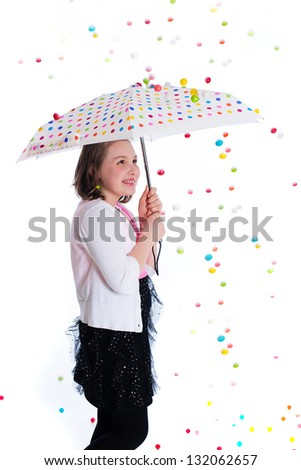 Gumball storm falling on an umbrella over a child. - stock photo