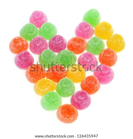 gumdrops of different colors forming a heart on a white background - stock photo