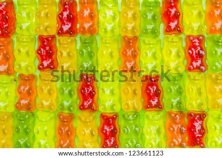 Gummibears in a row on green background - stock photo