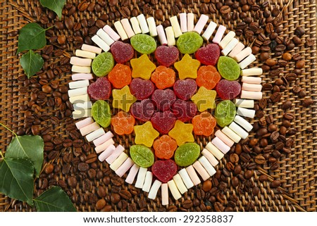 Gummy candies and marshmallow arranged in heart shape on table close up - stock photo