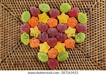 Gummy candies arranged in heart shape on wicker background - stock photo