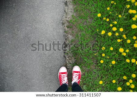 Gumshoes on urban grunge background of asphalt. Conceptual image of legs in boots on city street. Feet shoes walking in outdoor. Youth Selphie Modern hipster  - stock photo