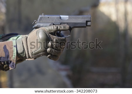 gun and camouflage gloves - stock photo