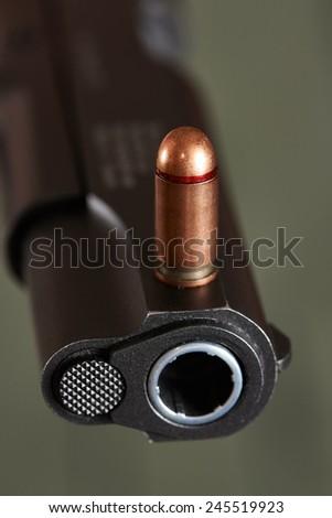 Gun and cartridge on khaki color background - stock photo