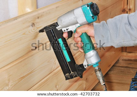 gun construction shoot    the nails in the wooden wall - stock photo