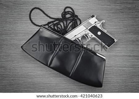 Gun in a purse, Woman bag with gun hidden, Woman's clutch purse with gun and accessories, Handgun and accessories falling from a woman's purse. (Black & White) - stock photo
