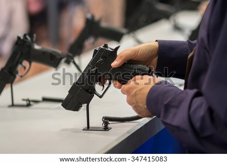 Gun in his hand. Exhibition and sale of weapons - stock photo