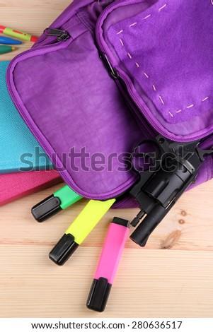 Gun in school backpack on wooden background - stock photo