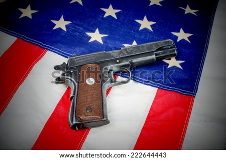 gun laid on the American flag close-up - stock photo