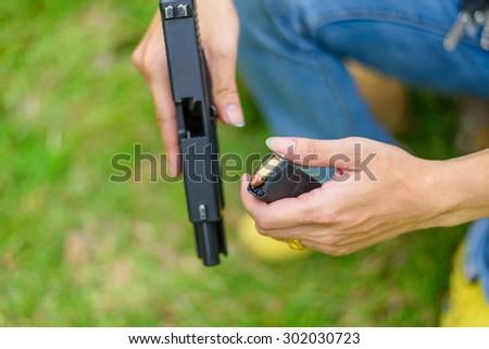 Gun man hand on green background - stock photo