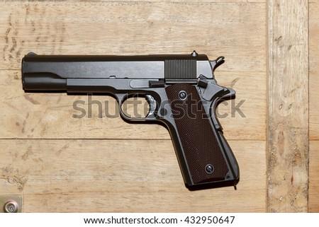 Gun on old wood background - stock photo
