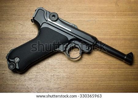 Gun on wooden background - stock photo