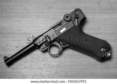Gun on wooden background black and white tone - stock photo