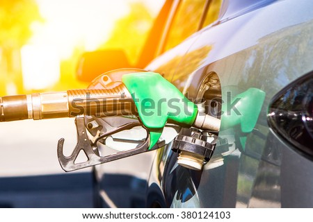 Gun petrol in the tank to fill. Car refueling concept. - stock photo