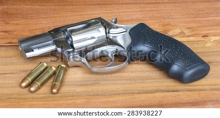 Gun placed on a table with bullet shells - stock photo