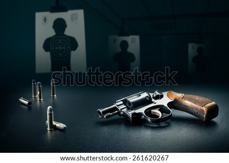 gun sitting on a table with bullet shells - stock photo
