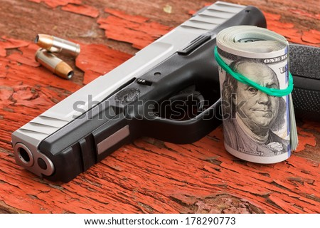 Gun with a roll of 100 dollar banknotes and two bullets lying on a grungy wooden surface with red peeling paint conceptual of crime, robbery, coercion, bribe or mob protection money - stock photo
