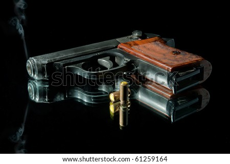 gun with bullet on a black - stock photo