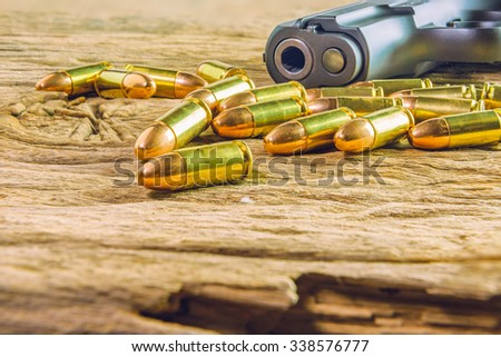 gun with bullets on wooden background - stock photo