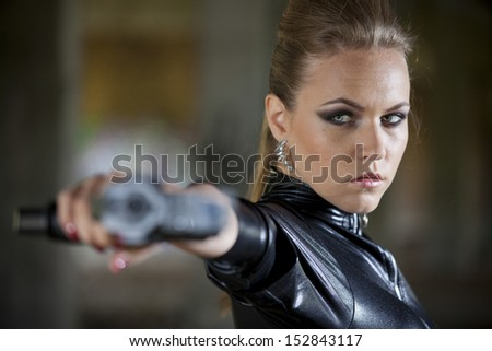 gun woman in fetish leather catsuit shooting - stock photo