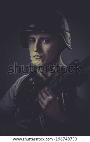 Gunfire, paintball sport player wearing protective helmet aiming pistol ,black armor and machine gun - stock photo