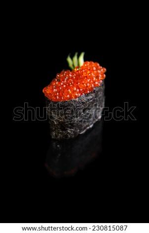 Gunkan Maki Sushi with red caviar on a black background - stock photo