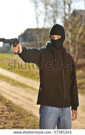 Gunman in black mask holding gun with silencer - stock photo