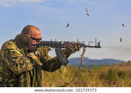 gunman shoots burst from Kalashnikov - stock photo