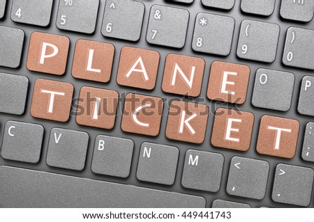 Gunmetal plane ticket key on keyboard - stock photo