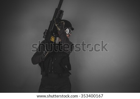 gunpowder, airsoft player with gun, helmet and bulletproof vest on gray background - stock photo