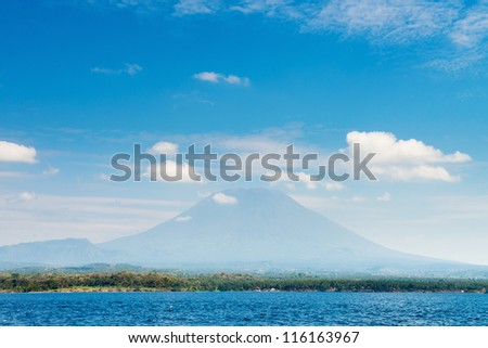 Gunung Agung the highest volcano on Bali island, Indonesia with blue cloudy sky and sea on front. - stock photo